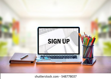 Open laptop with isolated white screen on old wooden desk with text SIGN UP