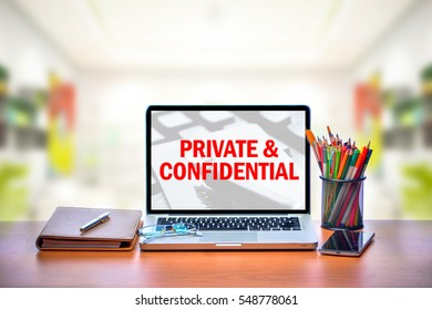 Open laptop with isolated white screen on old wooden desk with text PRIVATE & CONFIDENTIAL