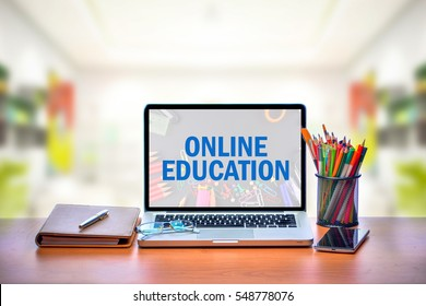 Open laptop with isolated white screen on old wooden desk with text ONLINE EDUCATION