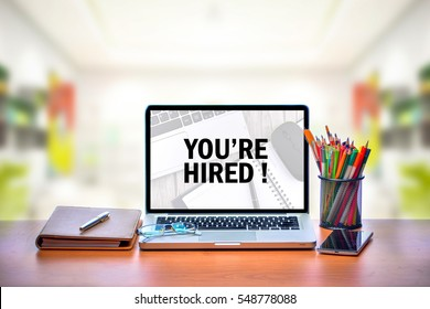 Open laptop with isolated white screen on old wooden desk with text YOU'RE HIRED