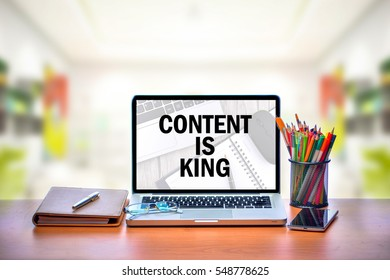 Open laptop with isolated white screen on old wooden desk with text CONTENT IS KING