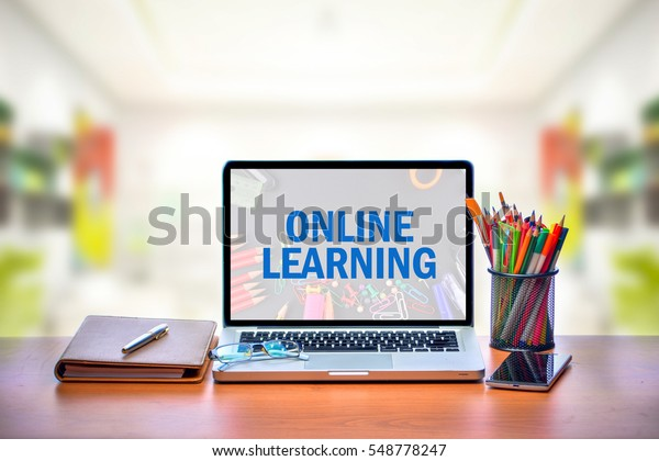Open laptop with isolated white screen on old wooden desk with text ONLINE LEARNING