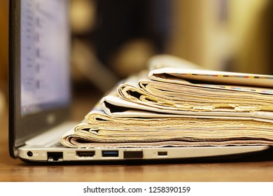 Open Laptop with Newspapers and Magazines on its Keypad. Business Journals with Headlines and Articles and Computer. News by Modern Gadget or Old-fashioned Tabloid Papers