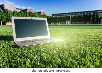 An open laptop on the campus lawn