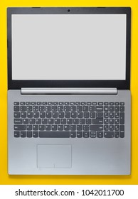 Open laptop with a white screen on a yellow background. Modern computer technologies. Top view.