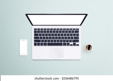 Open laptop with white smartphone and coffee on bright blue desk background. Devices with isolated screen for presentation. Mockup