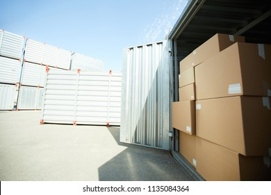 Open large metal container with stack of carboard boxes by day, container storage area