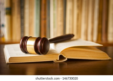 Open law book with a judges gavel resting on top of the pages in a courtroom or law enforcement office
