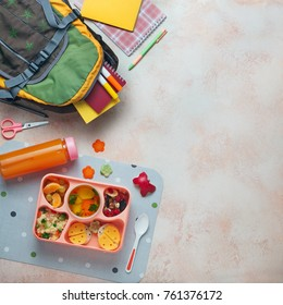 Open lunch box with healthy kid's lunch with vegetable soup, couscous salad and funny sandwiches near backpack and orange juice on beige background with blank space for text; top view, flat lay