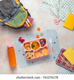 Open lunch box with healthy kid's lunch with vegetable soup, couscous salad and funny sandwiches near backpack and orange juice on beige background; top view, flat lay