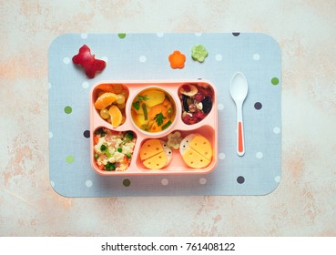 Open lunch box with healthy kid's lunch with vegetable soup, couscous salad and funny sandwiches on beige background; top view, flat lay