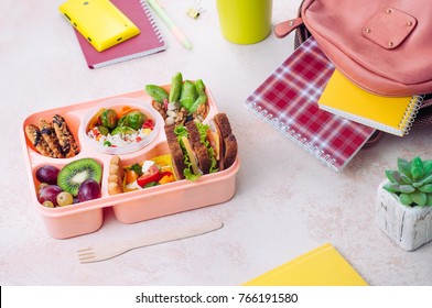 Open lunch box with healthy lunch with sandwiches, vegetable salad, fresh grape and kiwi, rice with grilled Brussels sprouts and nuts on the table near school backpack; selective focus