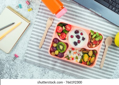 Open lunch box with healthy lunch with vegetable salad, berries in yougurt, fruits, rice with grilled Brussels sprouts and nuts on office table; top view, flat lay