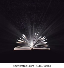 Open magic book, bewitched book glows in the darkness, magic light. Education. Dreamy image of a fairytale