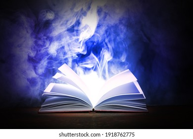 Open magic book on dark background
