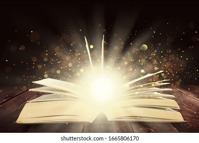 Open magic book on the table on a dark background