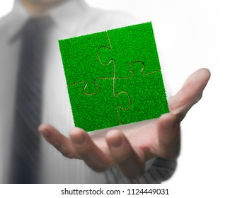 Open male hand with green grass of jigsaw puzzles, isolated on white background.