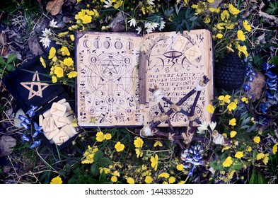 Open manuscript with moon lunar phases and mystic symbols.  Wicca, esoteric, divination and occult concept with magic objects for mystic rituals, Halloween, Beltane background