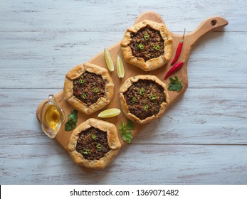 Open meat pies on a wood background. Top view.