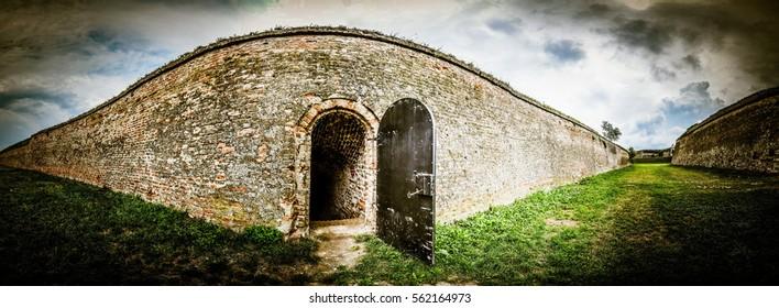Open metal door in old castle brick wall