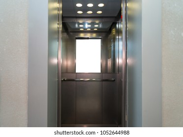Open metal elevator doors with a handrail and a mirror inside
