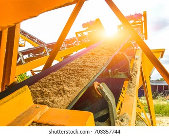 Open mines and processing plants for grinding sandstone and gravel to be used in the road and construction industry, and the evening sun.