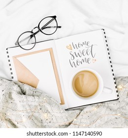 Open Mockup planner and Cup of coffee on bed with warm plaid. Copy space. Flat lay, top view