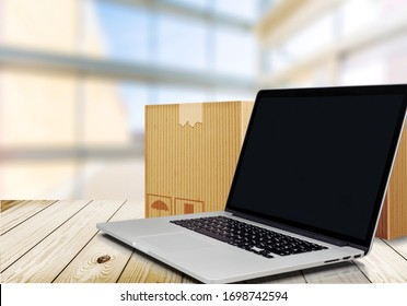 Open modern laptop computer at a desk and stack of cardboard boxes