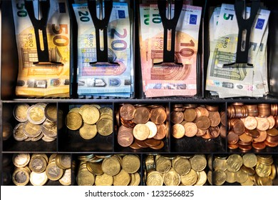 Open money drawer of a register in a European small business. Top view of bills organized into slots of a cash tray, with banknotes of 50, 20, 10 and 5 Euros, and coins of all Euro Zone denominations.