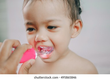 Open mouth of little girl during checking tooth and by dental mirror tools toy. Healthcare And Medicine Concept