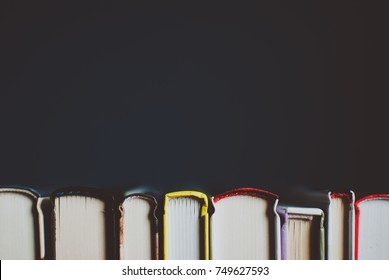 Open new colorful books standing on the wooden table. Closeup of pages. Abstract concept of knowledge, education, learning, and literature.
