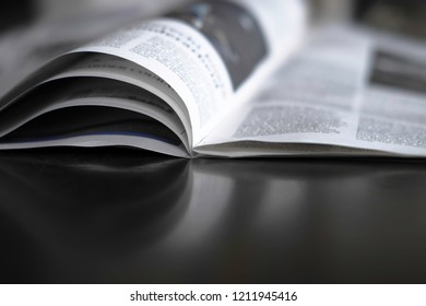 Open newspaper with swallow depth of field mirrored on a dark table