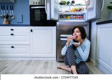 Open Night Sweet Indulgence. Woman Eating Near Refrigerator