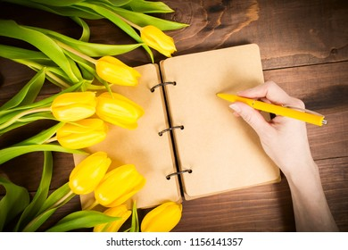 Open notbook with female hands holding yellow pen with yellow tulips, Woman's day or Mother's day concept, toned photos