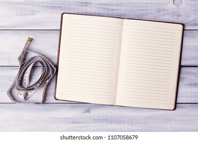 Open note pad with measuring tape over light wooden background