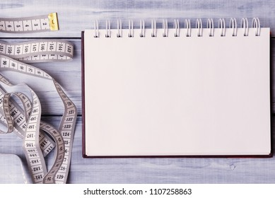 Open note pad and measuring tape on light wooden background.