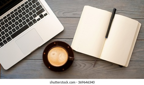 an open notebook with black pen on notebook pages, a silver laptop computer and a browns cup of coffee are lying next to an open notebook on a grey wooden table