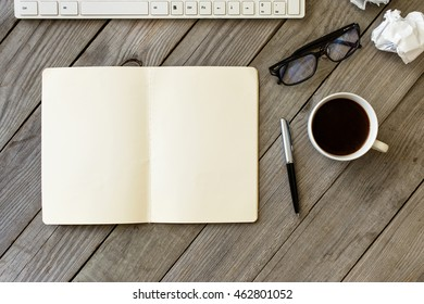 Open Notebook With Blank Pages, Pen, Glasses, Keyboard, Crumpled Paper And Cup Of Coffee On Wooden Table. Top View