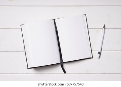 open notebook with blank pages and pen on white wooden desk