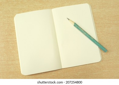 open notebook with blank pale yellow pages and old pencil on wooden desk