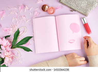 open notebook with blank pink pages, a bouquet of peonies, red lipstick and a female silver clutch on a purple background, top view