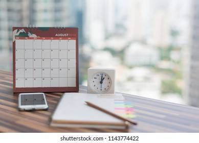 Open Notebook Calendar August 2018 with smartphone diary clock pencil blurred background modern office. Event organizer midyear half year planning, timetable, schedule. Calendar 2018 Concept.