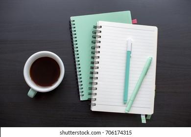 Open notebook with coffee cup and pens stationery on dark gray table