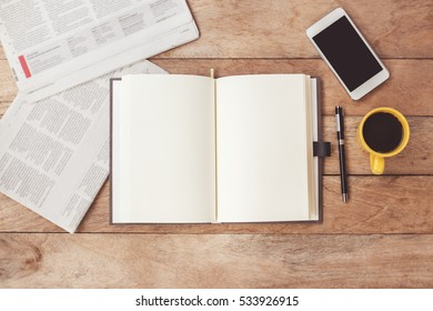 Open notebook with cup of coffee,newspaper,smartphone on wooden desk.