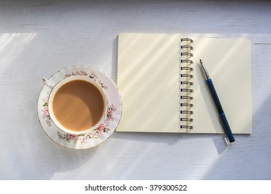 Open notebook and cup of tea on a sunny table top.