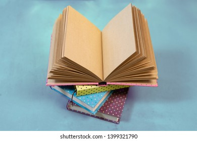 Open notebook with empty craft texture pages. Personal diary or a book with empty page. Back to school with stack of note books.