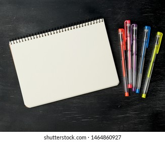 open notebook and gel pen on a black wooden background, top view, empty white sheets
