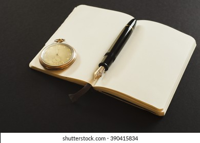 Open notebook with ink pen and golden pocket watch on black background
