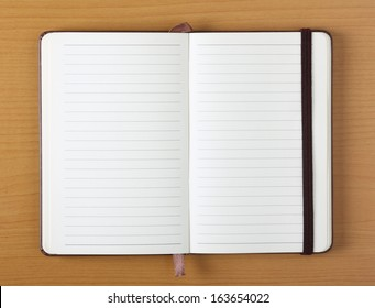 Open Notebook or Journal with blank lined pages for copy space on a plain wood background