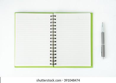 Open notebook with metallic ball pen. Top view.